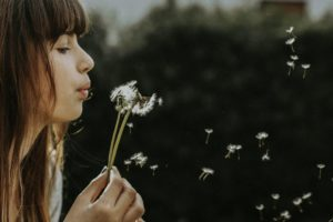 Woman Blowing a Dandelion
